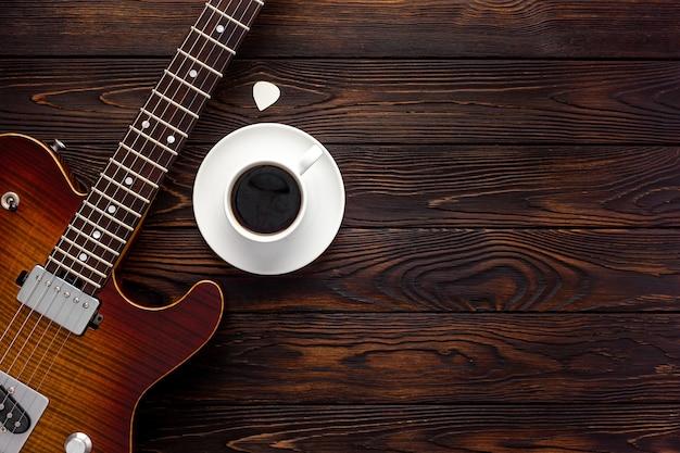 ヘッドフォンとコーヒーデスクトップを備えた美しいエレキギター