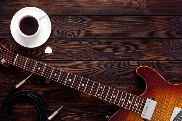 Красивая электрогитара в наушниках и кофейном столе