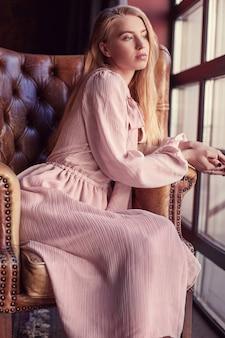 Красивая элегантная блондинка в розовом платье сидит в кожаном кресле