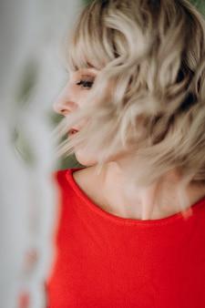 Красивая элегантная блондинка в красном платье с длинным рукавом на зеленой стене