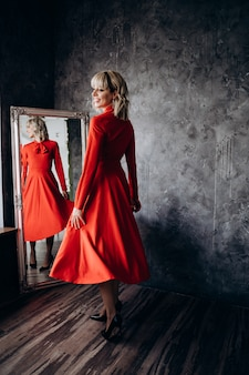 Красивая элегантная блондинка в красном платье с длинным рукавом на серой стене стоит перед зеркалом