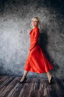 Красивая элегантная блондинка в красном платье с длинным рукавом на серой стене
