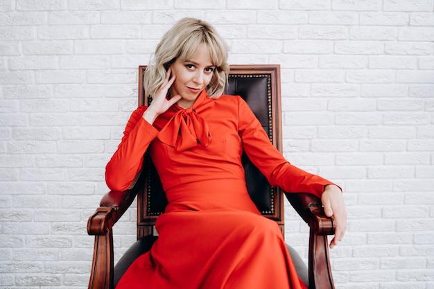 Красивая элегантная блондинка в красном платье с длинным рукавом на белой кирпичной стене сидит в коричневом кресле