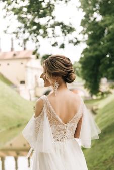 Красивая элегантная невеста на фоне старого замка