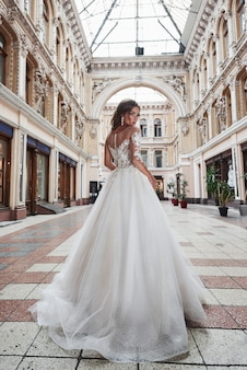 Beautiful, elegant bride with a perfect wedding dress, poses around beautiful architecture.