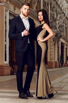 Красивая элегантная брюнетка с мужем гуляет по элям городских улиц. наслаждайтесь временем, одетым в черный классический костюм и длинное коктейльное платье.