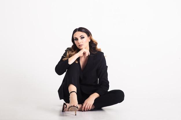 灰色の上に座っている美しいエレガントなビジネス女性