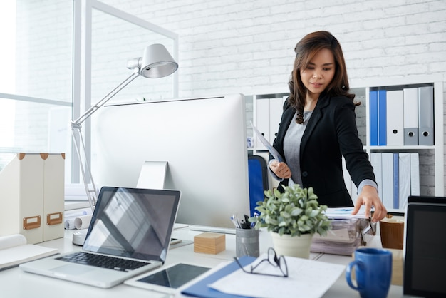 Beautiful elegant businesswoman taking document from stack on her desk when hurrying to meeting