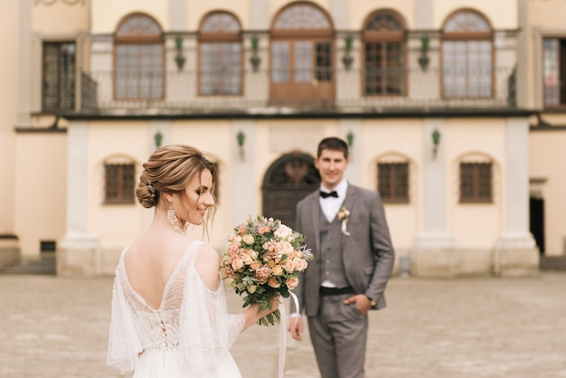 Beautiful elegant couple of newlyweds in love on  old building and paving stones, european wedding