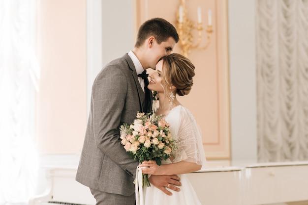Красивая элегантная пара влюбленных молодоженов в роскошном интерьере