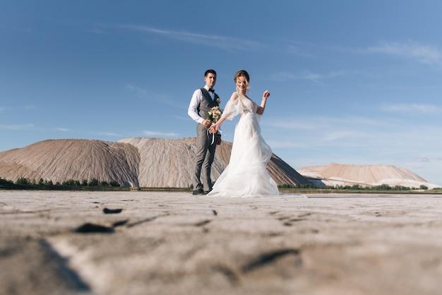 Красивая элегантная пара влюбленных молодоженов в соляные горы и карьеры