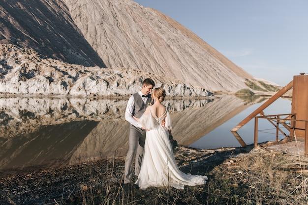 美しい自然の背景に恋をしている新婚夫婦の美しいエレガントなカップル