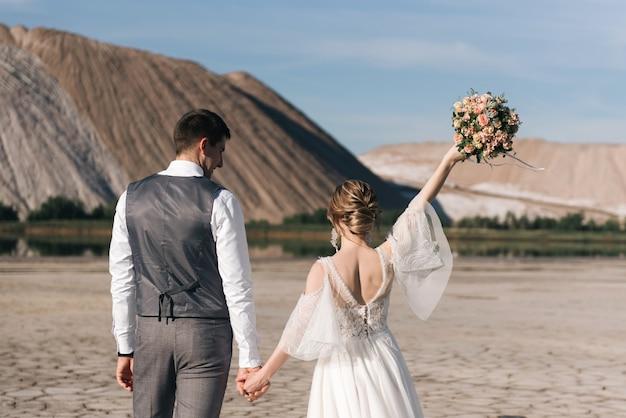 Красивая элегантная пара влюбленных молодоженов на соляных горах