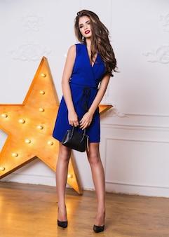 Bellissima modella elegante in abito da sera blu in posa instudio. indossare tacchi alti