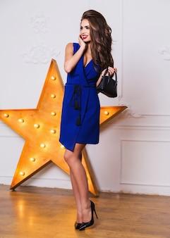 スタジオでポーズをとって青いパーティードレスで美しいエレガントなファッションモデル。かかとの高い着用