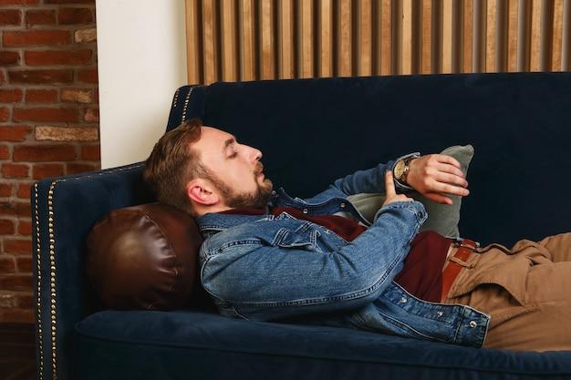 青いジャケットの美しいエレガントでファッショナブルな若い男がソファに座っています