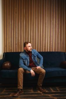 ジャケットの美しいエレガントでファッショナブルな若い男は、モダンなアパートと思考のソファに座っています
