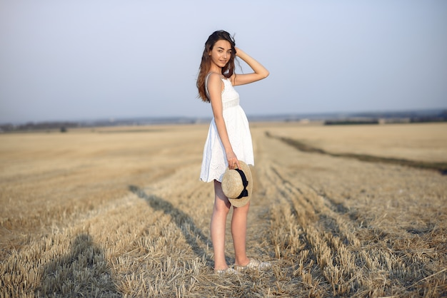 Beautiful elegant girl in a autumn wheat field