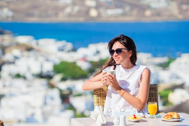 ミコノスの街の素晴らしい景色と屋外カフェで朝食を持っている美しいエレガントな女の子。リゾートレストランで海を望む高級ホテルのテラスでホットコーヒーを飲む女性。