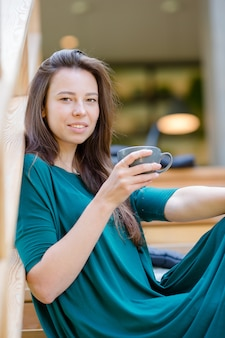 Beautiful elegant girl having breakfast at outdoor cafe. happy young urban woman drinking coffee