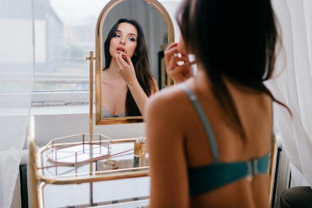 化粧台で化粧をしている下着の美しいエレガントな女の子