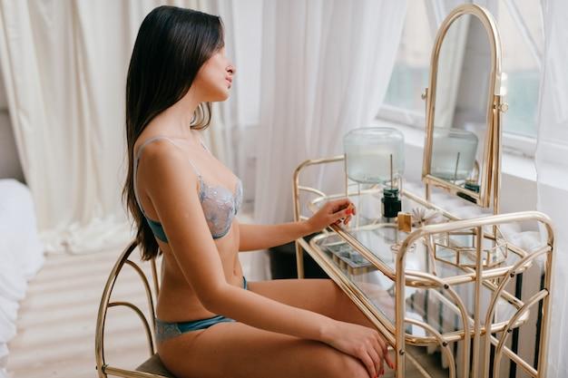 鏡を見ている下着の美しいエレガントな女の子