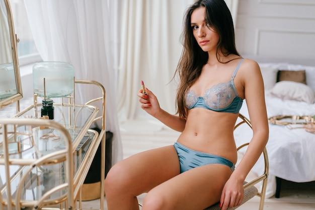 ドレッシングテーブルに座っている下着の美しいエレガントな女の子