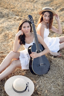 Beautiful elegant girls in a autumn wheat field
