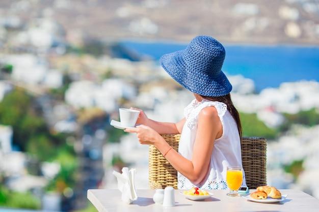 ミコノスの街の素晴らしい景色と屋外カフェで朝食を持っている美しいエレガントな女性。リゾートレストランで海を望む高級ホテルのテラスでホットコーヒーを飲む女性。