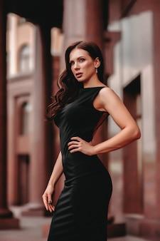Красивая элегантная модель в черном платье с размытым фоном коричневого здания