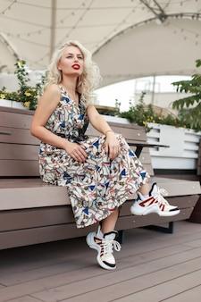 スタイリッシュな靴とパターンのファッションドレスの赤い唇を持つ美しいエレガントなモデルの女性は、通りの木製のベンチに座っています