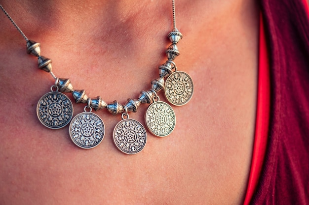 Beautiful and elegant necklace on the neck of a young happy woman. luxury and expensive jewelry glitters in the sun.