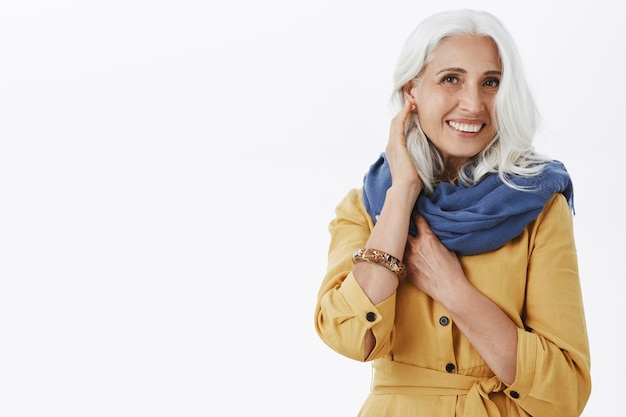 Beautiful elegant old woman with grey hair in stylish outfit smiling