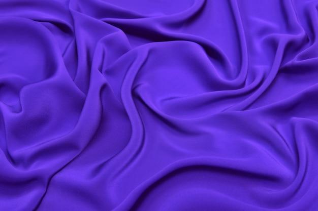 Красивая элегантная волнистая лиловая атласная шелковая роскошная ткань ткани текстуры с фиолетовым фоном.