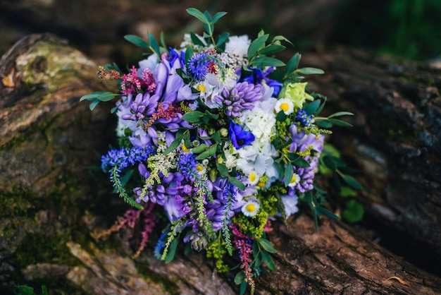 Beautiful elegant wedding bouquet with daisies and a variety of blue and purple flowers