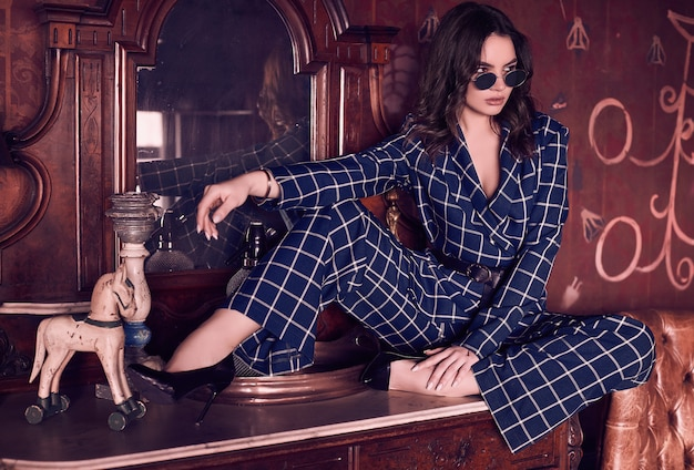 Beautiful elegant woman dressed in a blue checkered suit
