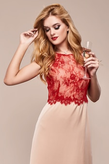 Beautiful elegant woman in fashionable dress with glass of champagne
