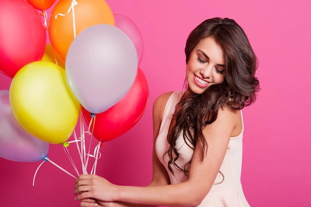 Beautiful elegant woman holding multi colored balloons