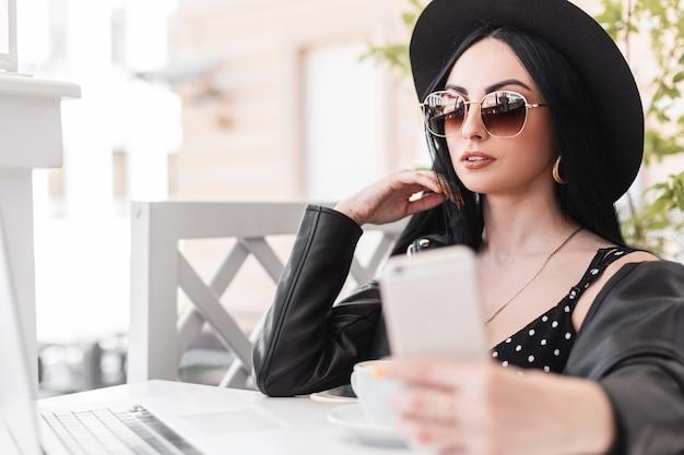 帽子と革のジャケットのドレスを着たサングラスの美しいエレガントな女性は、カフェのテーブルに座って、携帯電話で自分撮りをします。セクシーな女の子のモデルは、晴れた夏の日に屋外で自分自身を撮影します。