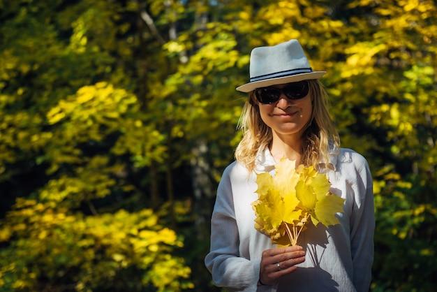 白いシャツと帽子の美しいエレガントな女性が立って、秋の都市公園で黄色の葉の花束と笑顔。