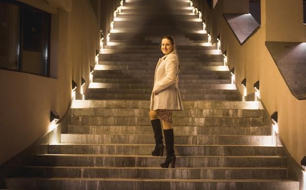 夜に照らされた階段でポーズをとる美しいエレガントな女性