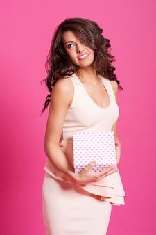 Bella donna elegante in posa con confezione regalo