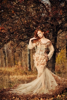 Beautiful elegant woman standing in the autumn forest in chiffon dress with yellow autumn leaves