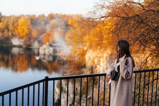 Красивая элегантная женщина, стоящая в парке осенью