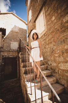 古い石造りの建物で階段を降りる美しいエレガントな女性
