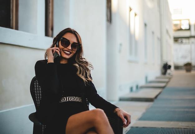 電話で話しているサングラスと美しいエレガントな女性。携帯電話で座っている女の子。