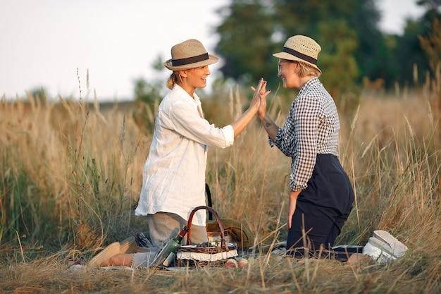 Beautiful elegant women in a autumn wheat field