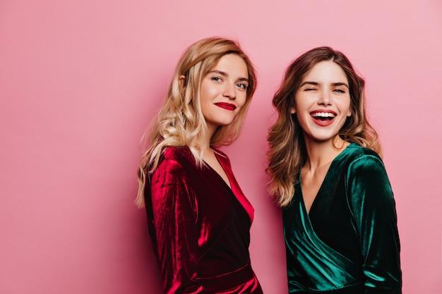 장미 빛 벽에 서있는 아름 다운 우아한 여성. 갈색 머리 여동생과 함께 포즈를 취하는 빨간 벨벳 드레스에 매혹적인 금발 소녀.