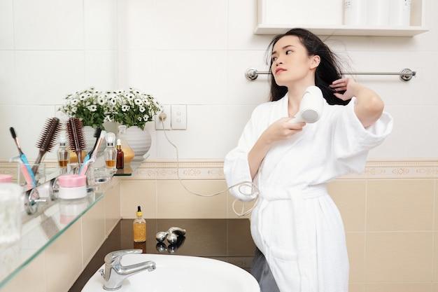 Красивая элегантная молодая азиатская женщина дует волосы после душа утром