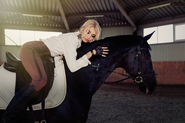 Beautiful elegant young blonde girl lies on a her black horse dressing uniform competition white blouse shirt and brown pants.